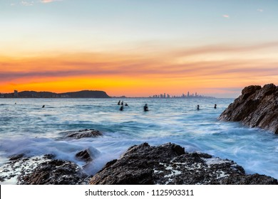 Ocean tide washing over the rocks at Currumbin Rock with a colourful sunset in the skies and surfers in the ocean.