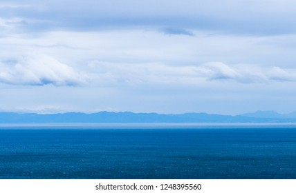Ocean view from expressway in Asahikawa, Hokkaido, Japan. Mountain and blue sea with cloudy sky.