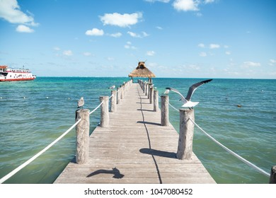 Ocean view from a pier with seagulls perched on either side of it and a grass roof at the end.