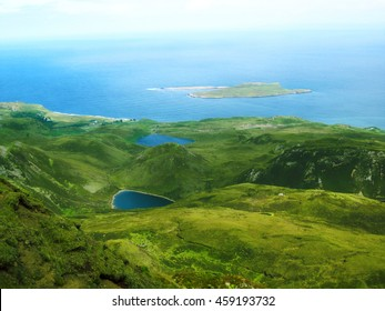 Ocean view from the rolling green hills on the Isle of Skye in Scotland, United Kingdom. Beautiful Scottish countryside with lakes, mountains, and sea.