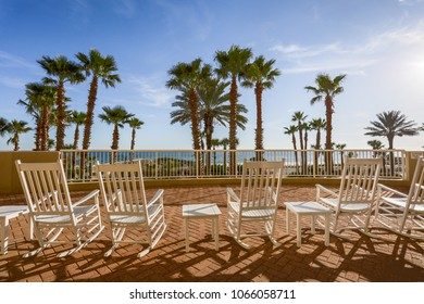 ocean view from tiled veranda rocking chairs and palm trees