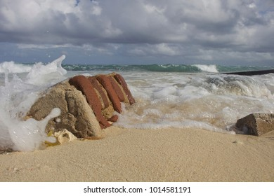 The ocean washes over part of a brick pillar tossed into the surf during Hurricane Irma. Camaguey province, Cuba - 2018.