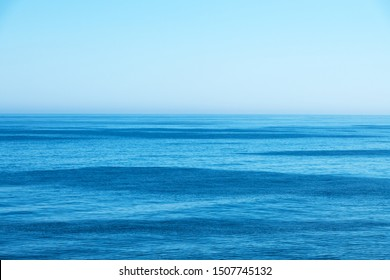Ocean water and blue sky abstract background. Sea water texture closeup
