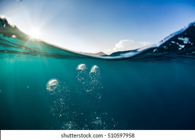 Ocean water line splits sky and underwaer part. Air bubbles in deep blue. Bright sun light and blue clear sky