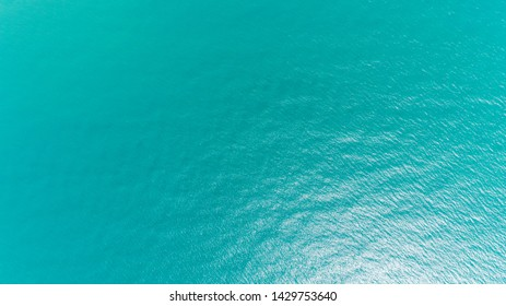 Ocean water texture. Aerial view of sea surface. Top view of transparent turquoise ocean water surface.