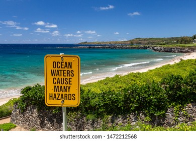 Ocean Waters Cause Many Hazards sign with view of Oneloa Beach, Maui, Hawaii
