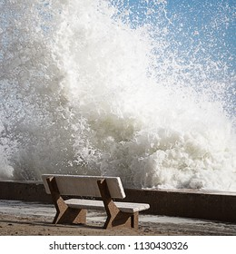 Ocean wave crashing high over a seawall and bench at Hampton Beach, New Hampshire, USA