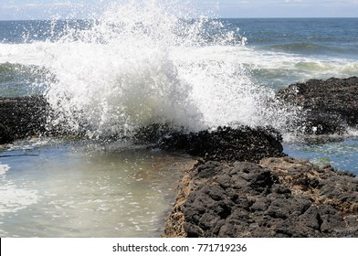 Ocean wave crashing on black rock formations along Oregon's coastal region.
