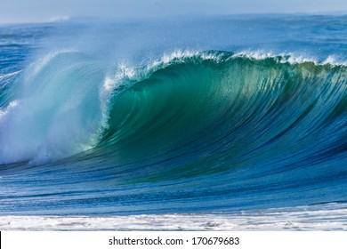 Ocean Wave Curl  Clean ocean wave rolling curling lip crashing on shallow sandbars.
