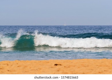 Ocean Wave Curling and Splashing with Blurred Sand in Foreground at North Avoca Beach on the NSW Central Coast of Australia