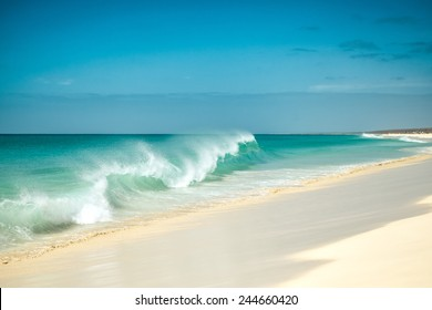 Ocean waves breaking at Cape Verde sandy beach in summer on a sunny day