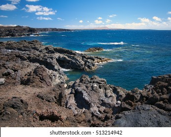 Ocean waves breaking on the rocky coast of hardened lava with caverns and cavities. Deep blue sky with white clouds and mountains and volcanoes on the horizon. Lanzarote, Canary Islands, Spain