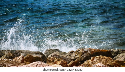Ocean waves crashing on rocky shore. Beautiful motion close up background.