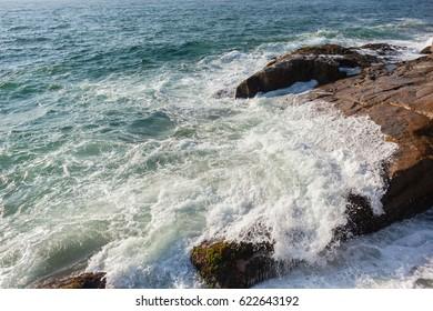 Ocean Waves Rocky Coastline Ocean waves crashing washing over large coastline rocks closeup overhead photo of natures power.