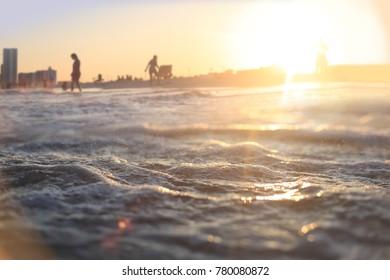 Ocean waves roll into beach goers feet at resort