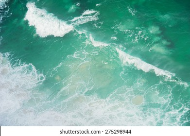 Ocean waves shot from above. The water is turquoise color and the waves have a diagonal path.