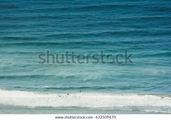 Ocean waves with surfers
