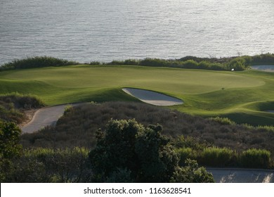 An oceanfront golf course in southern California has a neatly groomed green in late afternoon sunlight, bordered by sand traps and rough vegetation.