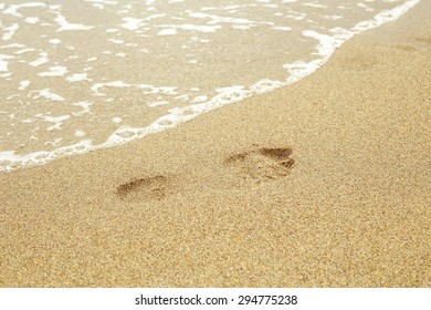Oceanfront trail from the foot in the sand. Jogging on the sandy beach. Leisure at sea. The coolness of the ocean. Footprint in the sand. Sandy coast. Beach vacation. Sea foam and wave.