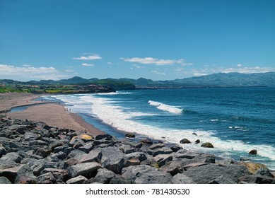 Oceanic coast of Sao Miguel island of Azores, Portugal, near the Ribeira Grande town, with mountains visible on skyline and sand beach on left side.