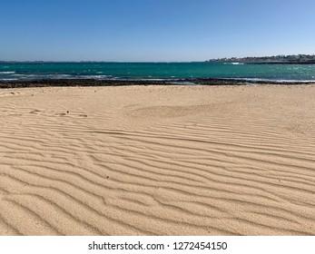Oceanside beach texture, sand waves on the beach of Corralejo, Fuerteventura