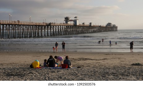 Oceanside, CA / USA - April 12, 2019: people enjoying the beach by the Oceanside Pier near sunset