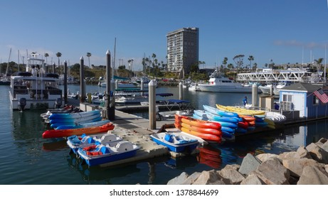 Oceanside, CA / USA - April 22, 2019: Colorful rental kayaks are stacked at the Oceanside Harbor