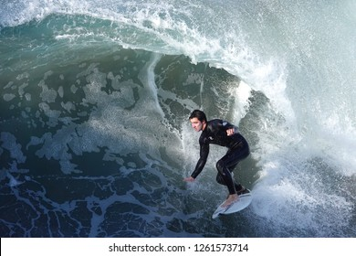 Oceanside, CA / USA - December 18, 2018: A young surfer on a big wave