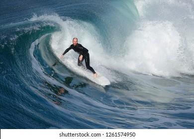 Oceanside, CA / USA - December 18, 2018: Older male surfer in a beautifully curling wave