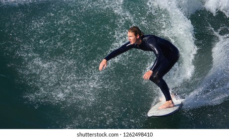 Oceanside, CA / USA - December 19, 2018: Male surfer in his 20's riding a wave