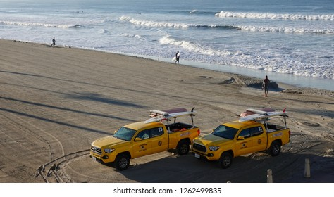 Oceanside, CA / USA - December 19, 2018: Early morning on Oceanside Beach, with lifeguard trucks parked on the raked sand