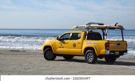 Oceanside, CA / USA - December 19, 2018: Yellow Toyota Tacoma lifeguard vehicle on beach