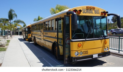 Oceanside, CA / USA - June 7, 2018: Yellow school buses parked in front of a California school on a sunny day