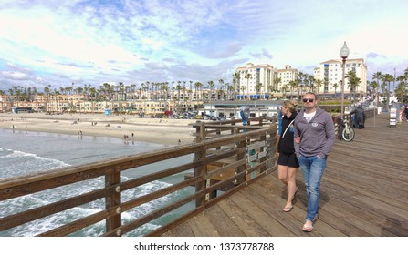 Oceanside, CA / USA - March 10, 2019: A couple, possibly tourists, stroll onto the Oceanside pier and take in the scenery