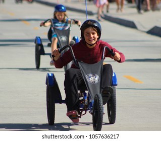 Oceanside, CA / USA - March 29, 2018: A boy is having fun racing a girl on a rented Chopper tricycle on the Oceanside beach walk