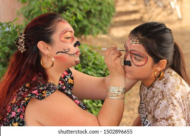 Oceanside, CA / USA - October 28, 2018: A mother paints her daughter's sugar skull (Catrina) makeup, getting ready for Day of the Dead celebration