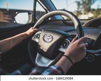 Oceanside, California / USA - June 16, 2018: Girl driving, Prius steering wheel