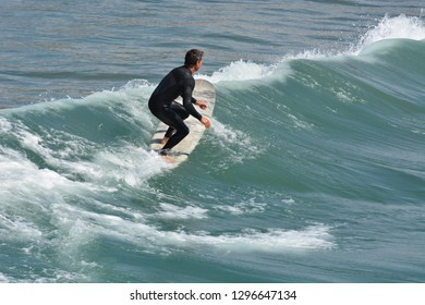 Oceanside, California / USA - March 20, 2014:  Surfer enjoys the waves on the Pacific Coast on a warm spring day.