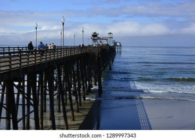 Oceanside, California / USA - March 23, 2018: A beautifully sunny spring day in southern California with huge fluffy white clouds at the pier.