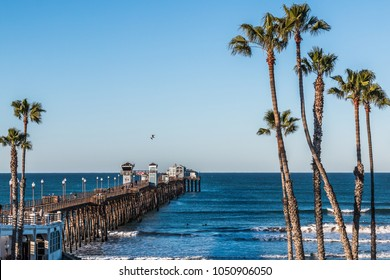 OCEANSIDE, CALIFORNIA/USA - FEBRUARY 24, 2018:  People fish and enjoy the view on the Oceanside fishing pier, while surfers wait for waves nearby.  The pier was originally built in San Diego in 1888.