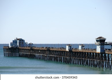 OCEANSIDE, UNITED STATES - DECEMBER 25: Visitors and Tourists walk in fine weather over the Oceanside Pier on December 25, 2015 in Oceanside / Oceanside Pier