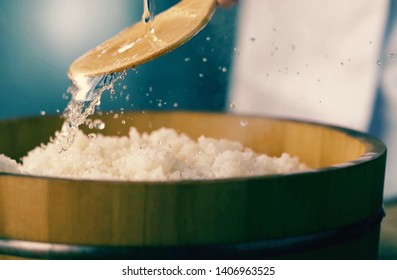 Ocet pours a spoon into the pan with rice