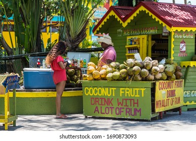 Ocho Rios, Jamaica - April 22, 2019: Ice Cold Coconut Fruit Drink with Rum stall/corner shop in rasta colors at the Ocho Rios Cruise Ship Port in the streets of Ocho Rios, Jamaica.