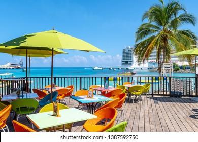 Ocho Rios, Jamaica - April 23 2019: Tropical island Caribbean color chairs & tables at Margaritaville Ocho Rios Restaurant and Sports Bar on the beach in Saint Ann. Norwegian Epic Cruise Ship in port.