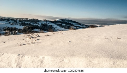 Ochodzita hill with dispersed settkement of Koniakow village bellow in Beskid Slaski mountains in Poland during winte day with snow and blue skyr