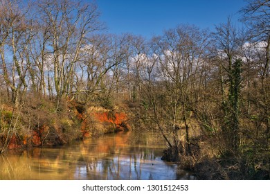Ochre colored river bank of the Agout River in Gourjade Park Castres in Southern France