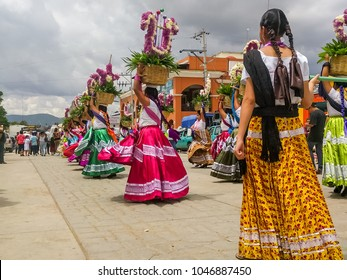 OCOTLAN DE MORELOS, OAXACA, MEXICO-July 24, 2017. Mexican women dancing in the streets and wearing colorful traditional costumes clothing at the annual Guelaguetza festival.