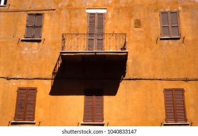 An ocre facade with windows and brown shutter, and a balcony with its shadow