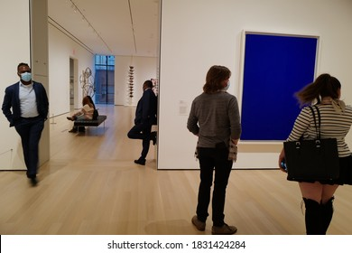 """Oct 05, 2020 Staffs and visitors at MoMA, Museum of Modern Art looking at Yves Klein """"BLUE MONOCHROME 1961""""with masks after the lockdown from Covid-19, Manhattan, New York City, USA"""