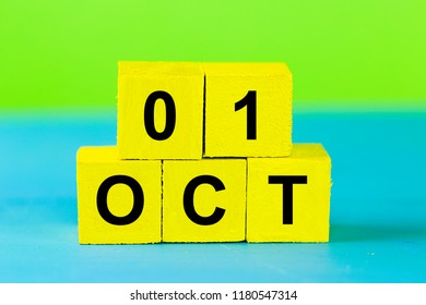OCT 1, yellow cube calendar on blue wooden surface with copy space